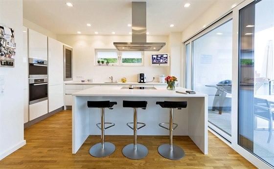 Kuchyňská linka z bíle lakovaných MDF desek ve vysokém lesku je doplněna varným ostrůvkem s barovým sezením. Za prosklenou stěnou je umístěno venkovní stolování.