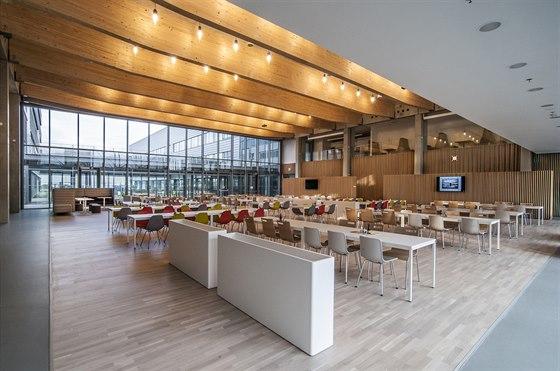 Středobodem sídla FEI je jídelna z akusticky pohlcujícího materiálu a s designem v ladných křivkách. Neformální dojem podtrhuje tlumené osvětlení.