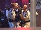 Záchranáři pečují o rukojmí z kavárny v centru Sydney (15. rposince 2014)