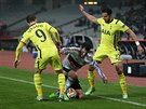 Pedro Franco z Besiktase se snaží udržet míč proti dvojici hráčů z Tottenhamu. Vlevo je Roberto Soldado, vpravo Nacer Chadli.