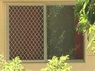 Okno domu v Cairns, ve kter�m bylo nalezeno osm zavra�d�n�ch d�t�.