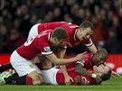 NEKONEČNÁ RADOST NA OLD TRAFFORD. Spoluhráči z Manchesteru United gratulují Waynemu Rooneymu (dole) k trefě ve šlágru s Liverpoolem.