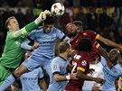 BITVA VE VZDUCHU. Joe Hart, brankář Manchesteru City, vyráží míč před hráči AS Řím.