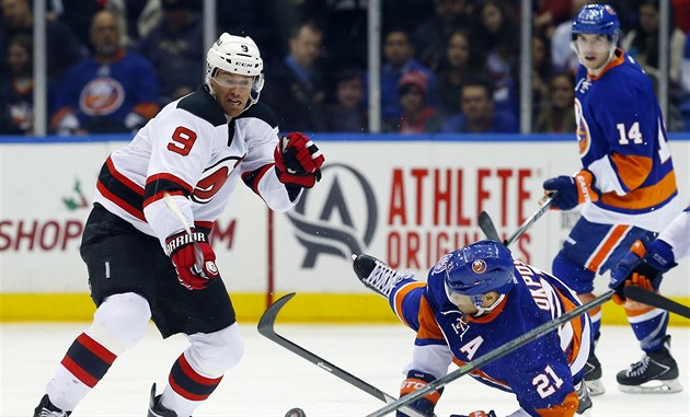 Martin Havlát (vlevo) z New Jersey bojuje s obranou Islanders. Na led padá Kyle...