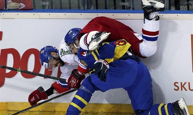 �védský hokejista Daniel Rahimi ost�e atakuje �eského úto�níka Jakuba Klepi�e.