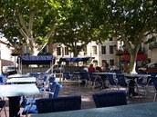 Kavárna v Capestang měla místo klasických stolečků modro-bílo pruhované obrovské houpací lavice se stříškou proti slunci.