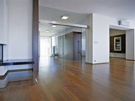 Celou jihozápadní polovinu domu zaujímá obývací pokoj spojený s jídelnou. Dveře z čirého skla uvolňují prostup světla a průhled napříč domem přes halu až do nového zádveří.