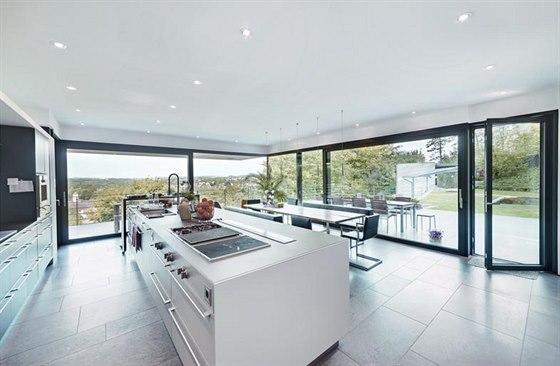 Rozlehlá obytná kuchyň v přízemí je ze dvou stran obklopena plně prosklenými stěnami. Kombinace pevně zasklených ploch, posuvných ploch a skleněných dveří umožňuje maximální otevření do zahrady, navíc s bezbariérovým přechodem.