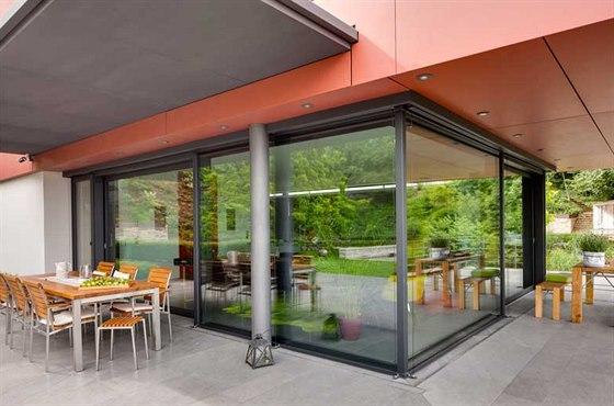 Architektura domu se vyznačuje plynulými přechody z interiéru do exteriéru. Rohovou kuchyň zvenku obklopují dvě stíněné terasy dlážděné stejným kamenem jako podlaha v domě. Obklad fasády v přesahující části plynule přechází v podhled s integrovaným osvětlením. Prosklené nároží se obešlo bez masivních konstrukčních prvků.