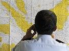 Důstojník u mapy v krizovém centru zřízeném na letišti v indonéské Surabáje.