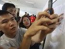 Lidé se v krizovém centru zřízeném na letišti v indonéské Surabáje snaží získat informace o svých blízkých ze ztraceného airbusu společnosti AirAsia .