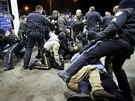 Policisté z amerického St. Louis zasahují na čerpací stanici na předměstí Berkeley, kde byl zastřelen černošský mladík. Dav lidí ignoroval policejní pásku a vtrhl na místo činu (24. prosince 2014).