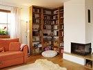 Společný obývací prostor zahřívá rohový krb s žulovou deskou a na dotek teplá a příjemná dubová podlaha. Rohová knihovna byla vyrobena na míru.