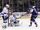 Radko Gudas z Tampa Bay už jen sleduje, jak si vede jeho branář Andrej Vasilevskij proti pokusu Anderse Leeho z NY Islanders.