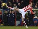 Peter Crouch ze Stoke City se natahuje po míči.