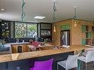 Život vnáší do interiéru drobné zařízení a hravé detaily, jako je například tyrkysová barva na sedacím nábytku nebo lustrové kabeláži nad barem u kuchyňského koutu.