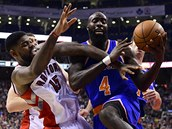 Quincy Acy z New York Knicks (vpravo) zakon�uje, brání ho Amir Johnson z...