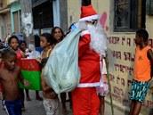 Santa Claus prochází chudinskou čtvrtí Mare na severu Ria De Janeiro a rozdává dárky dětem.