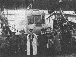 Druh� Ilja Muromec s�rie B (v�r.�. 135) s kanonem r�e 37 mm. Postava ve sv�tl�m pl�ti je ministr v�lky V. A. Suchomlynov, vedle n�ho, nejbl�e kanonu, stoj� M. V. �idlovskij, p�edseda p�edstavenstva RBVZ a pozd�j�� velitel Eskadry vzdu�n�ch kor�b�. Dal�� mu� v civilu, stoj�c� vpravo vep�edu mezi dv�ma uniformovan�mi, by podle viz�e mohl b�t konstrukt�r I. I. Sikorskij.