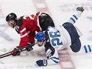 Darnell Nurse (vlevo) z Kanady a Sebastian Aho z Finska se během juniorského MS po vzájemném souboji ocitli na ledě.