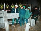 Dělníci stavějí zeď za dohledu strážníků